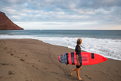 Spain, Tenerife, boy carrying surfboard on the beach - p300m1188949 by Simona Pillola