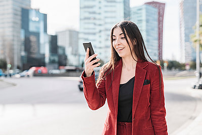 Surprised businesswoman looking at smart phone while standing in city - p300m2265927 by COROIMAGE