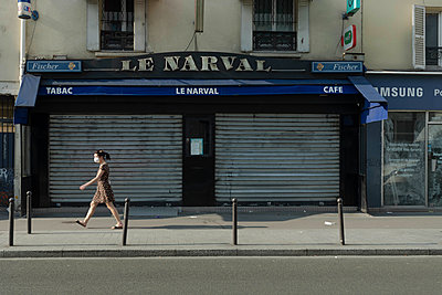 Woman walking with a mask in the street - p445m2176727 by Marie Docher