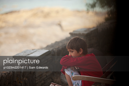 Pensive boy sitting along rock wall - p1023m2201417 by Sam Edwards