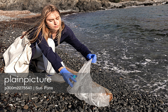 Woman collecting plastic while crouching on pebbles - p300m2275540 by Sus Pons