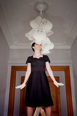 Woman in black dress on a ladder under a ceiling lamp - p1105m2244897 by Virginie Plauchut
