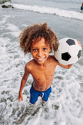 Portrait of a smiling boy holding a football on the beach - p300m2132222 von DREAMSTOCK1982