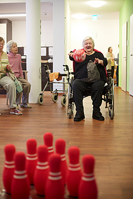 Age demented senior woman bowling with foam ball in a nursing home - p300m2219180 by Heinz Linke