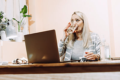 Senior woman drinking water during online consultation at home - p300m2240403 by Eloisa Ramos