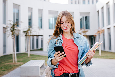 Smiling young blond female student using smart phone at university - p300m2241696 by Tania Cervián
