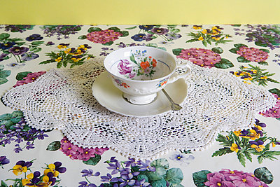 A cup of tea on a floral tablecloth - p3016836f by Serge