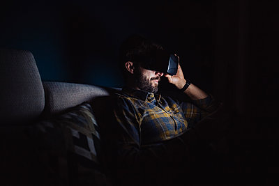 Bearded mid adult man sitting on sofa in darkness looking down through virtual reality headset - p924m2097326 by Eugenio Marongiu