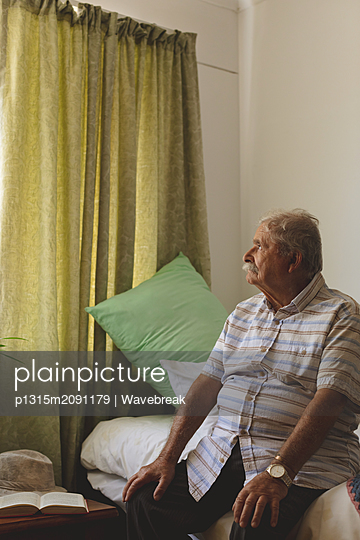 Senior man looking outside the window while sitting alone at nursing home - p1315m2091179 by Wavebreak