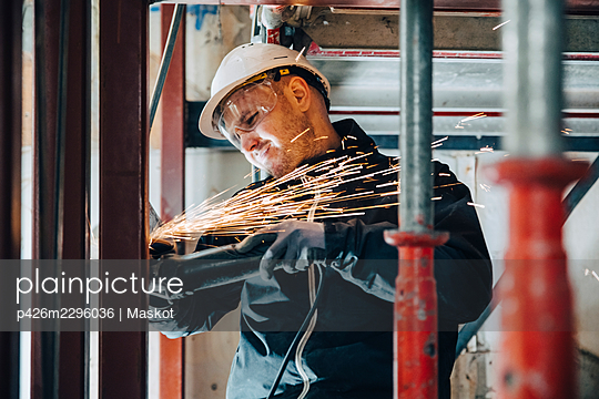 Male construction worker cutting metal with machinery at site - p426m2296036 by Maskot