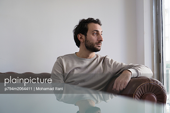 Man sat on sofa looking away  - p794m2064411 von Mohamad Itani