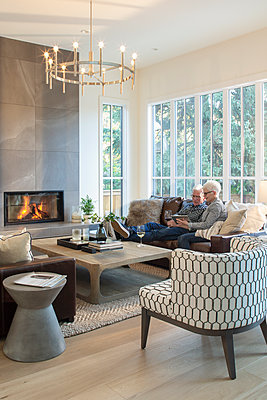 Senior couple relaxing on sofa, using digital tablet and drinking wine by fireplace - p1192m2047666 by Hero Images