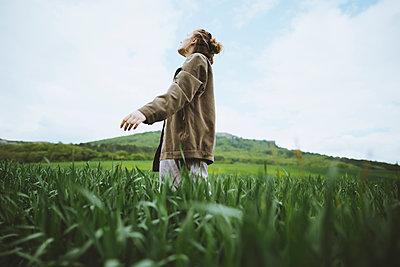 Woman wearing jacket in field in Crimea, Ukraine - p1427m2163658 by Oleksii Karamanov