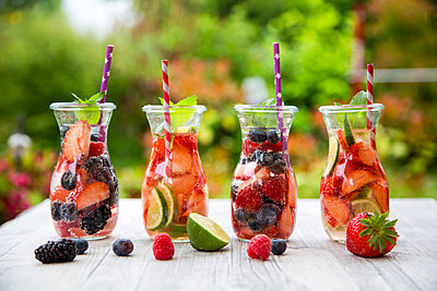 Four glass bottles of detox water infused with different fruits - p300m1153867 by Sandra Roesch