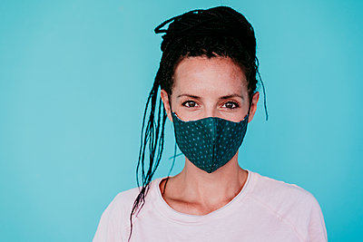 Confident woman wearing protective face mask while standing against turquoise background - p300m2220825 by Eva Blanco