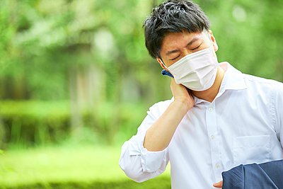 Young Japanese businessman wearing mask in the hot Summer downtown Tokyo - p307m2261312 by Naoki Morita
