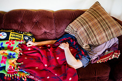 Man sleeping on sofa with pillow over head - p343m1447155 by Steve Glass
