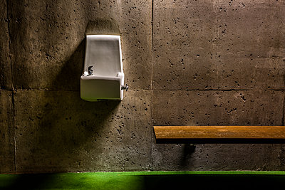 Water fountain and a wooden bench attached to a concrete wall. - p397m2015242 by Peter Glass