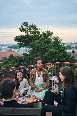 Happy friends enjoying social gathering on terrace during sunset - p426m2074323 by Maskot