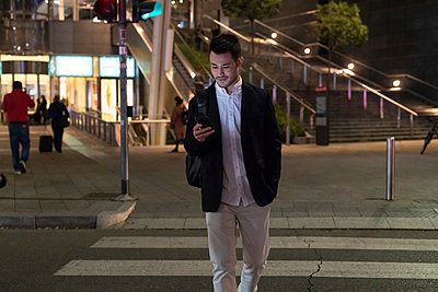 Young businessman on pedestrian crossing at night looking at smartphone, Milan, Italy - p429m2051136 by Garage Island Crew