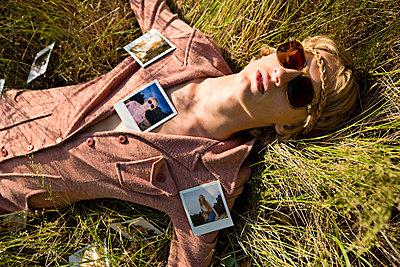 Teenage boy wearing sunglasses lying on grass with photographs - p5282409 by Tobias Duveskog