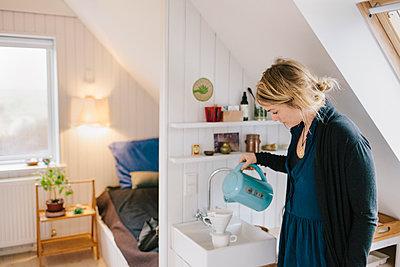 Junge Frau brüht Kaffee auf  - p586m1122927 von Kniel Synnatzschke