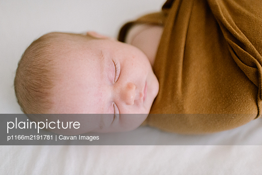 Closeup of newborn baby sleeping in brown swaddle - p1166m2191781 by Cavan Images
