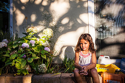 Portrait of girl sitting at backyard - p1166m1099515f by Cavan Images