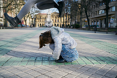 Excited girl and boy playing on street - p1166m2193871 by Cavan Images