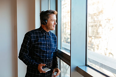 Businessman with headphones and cell phone looking out of window - p300m1562865 by Bonninstudio