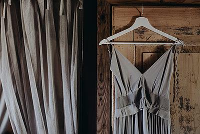Grey dress hanging at wooden door - p300m2059804 von Alberto Bogo