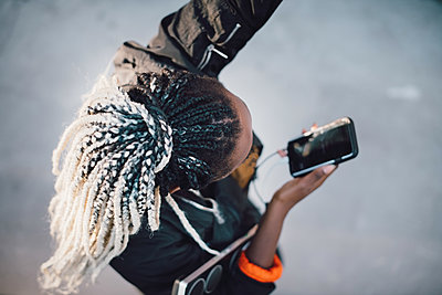 High angle view of teenage girl with dreadlocks dancing while holding smart phone at skateboard park - p426m2072343 by Maskot