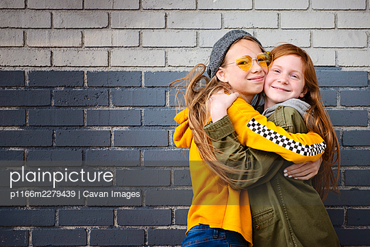 Two tween girls, best friends hugging. - p1166m2279439 by Cavan Images