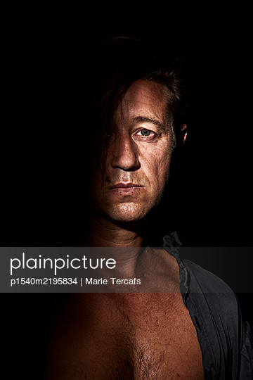Dramatic portrait of a man on a black background - p1540m2195834 by Marie Tercafs
