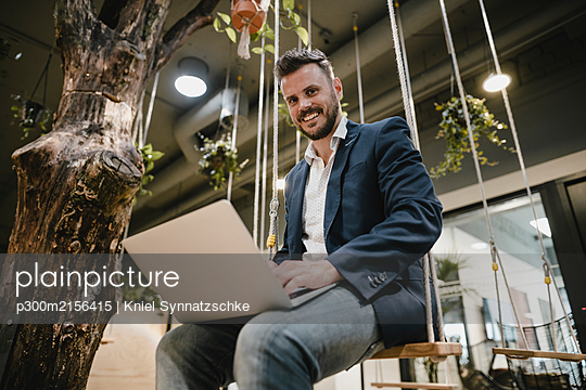 Businessman using laptop in coworking space, sitting on swing - p300m2156415 by Kniel Synnatzschke