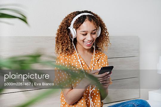 beautiful smiling hispanic listening to music on bed, Madrid, Spain - p300m2287467 von Eva Blanco