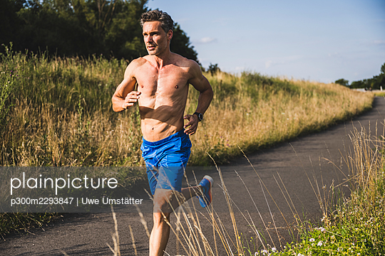 Shirtless sportsman running on road during sunny day - p300m2293847 by Uwe Umstätter