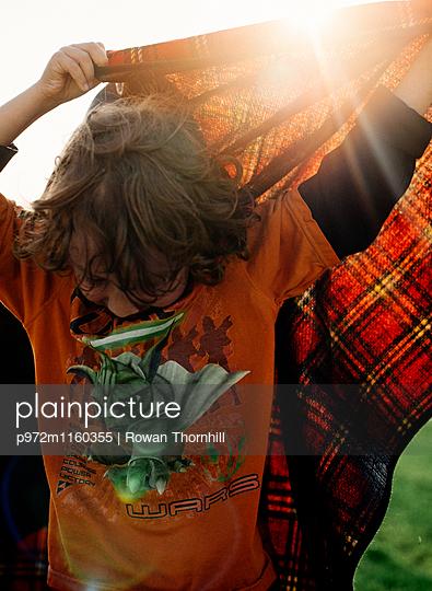 Junge spielt mit einer Wolldecke - p972m1160355 von Rowan Thornhill