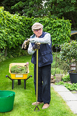 Senior man holding bucket with weeds - p1026m1164178 by Patrick Frost