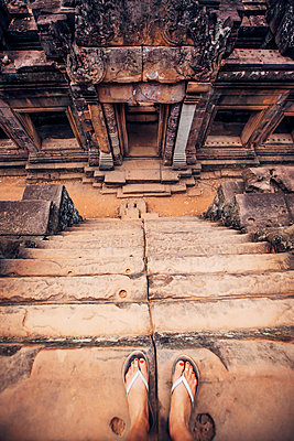Low section of woman standing on steps at Angkor Wat temple - p1166m1150962 by Cavan Images