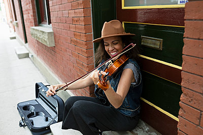 Happy woman playing violin on sidewalk - p1192m2123522 by Hero Images