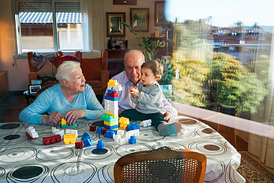 Great-grandparents and baby girl playing together with plastic building bricks at home - p300m1563134 by Gemma Ferrando