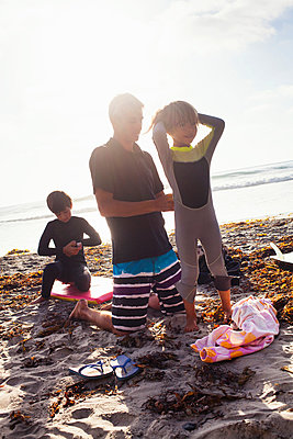 Father and children preparing to surf - p429m884154 by Yew! Images
