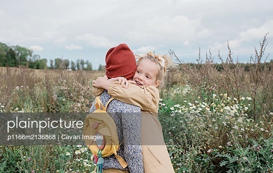 sister hugging her brother stood in a field of wild flowers in fall - p1166m2136868 by Cavan Images
