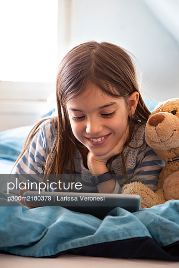 Portrait of smiling girl lying on bed with teddy bear using digital tablet - p300m2180379 by Larissa Veronesi