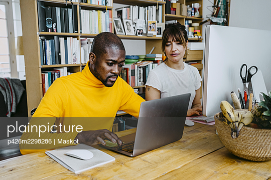 Male freelancer using laptop sitting by woman at table - p426m2298286 by Maskot