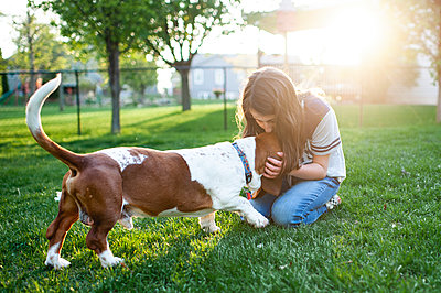 Tween girl kissing Basset Hound dog on head in the green grass at home - p1166m2146816 by Cavan Images
