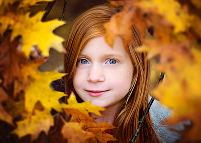 Red Haired Girl Looking Through Yellow Fall Leaves - p1166m2147080 by Cavan Images