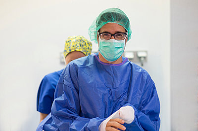 Male surgeon wearing eyeglasses with female coworker at hospital - p300m2243599 by Jose Luis CARRASCOSA