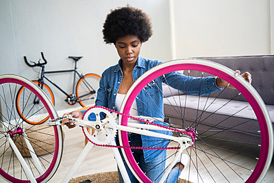 Afro hairstyle woman repairing bicycle at home - p300m2274763 by Giorgio Fochesato